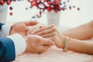 Dollar Photo groom holding bride's hands with ring at table