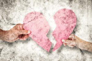 Adultery Photo Club Composite image of couple holding two halves of broken heart