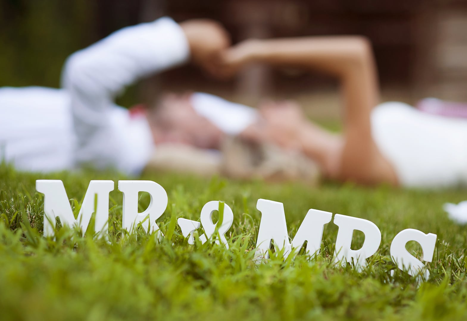 Truths about Weddings - graphicstock-happy-bride-and-groom-enjoying-their-wedding-day-in-green-nature-lying-on-grass_rATvQnnZ- copy