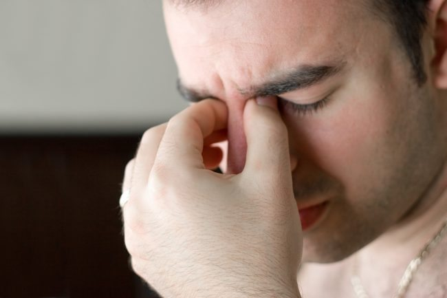 Adobe Stock A young man that has an intense headache.