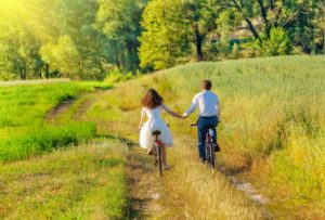 Young happy bride and groom ride bicycles in the meadow